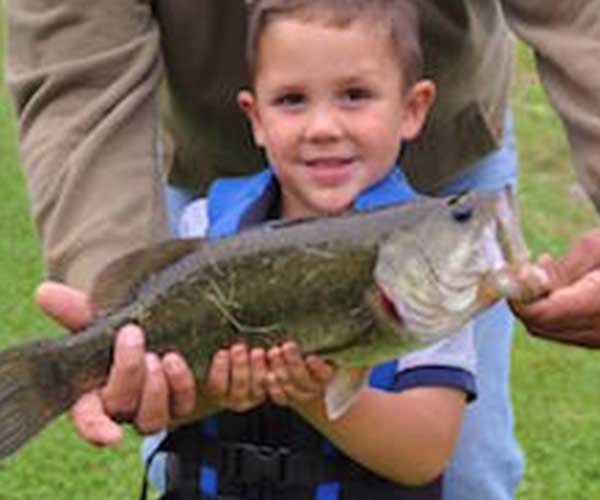little boy holding up a fish